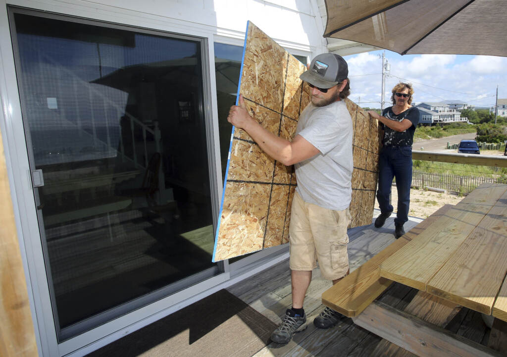 James Masog (center) and Gary Tavares move particle board into place to board up the sliding glass doors of a clients house in Charlestown, R.I., ahead of Hurricane Henri