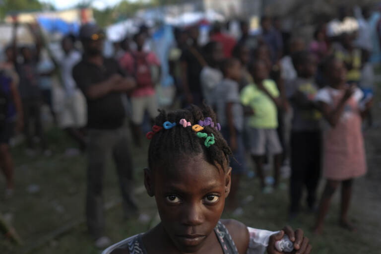 A girl waits with other earthquake victims for the start of a food distribution in Les Cayes, Haiti, Saturday, Aug. 21, 2021, seven days after a 7.2 magnitude earthquake hit the area. (AP Photo/Matias Delacroix)