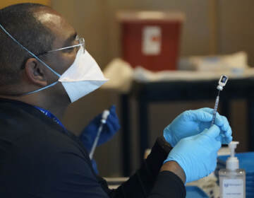 A health care worker fills a syringe with the COVID-19 vaccine.