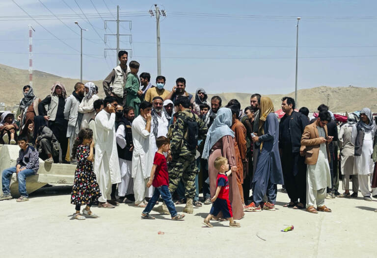 Hundreds of people gather near the international airport in Kabul
