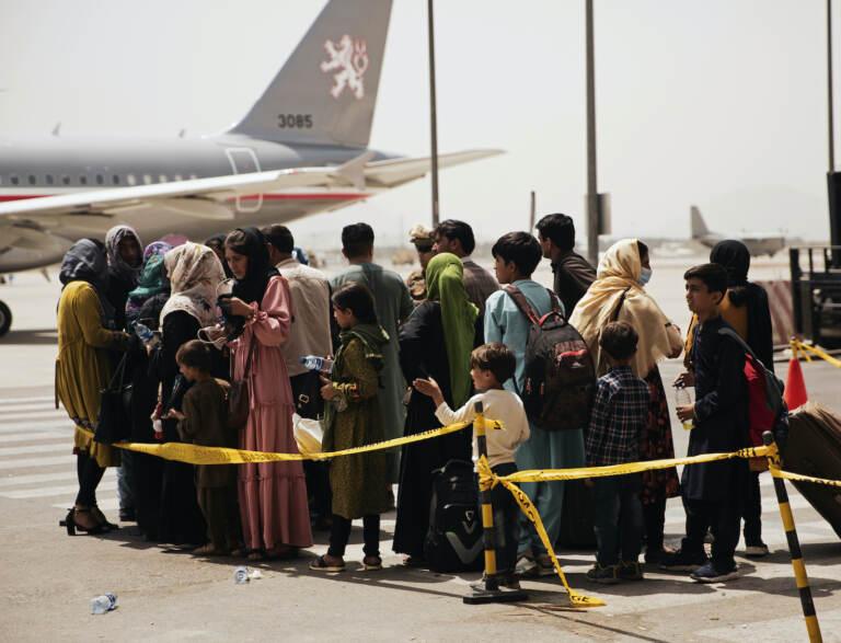 Civilians prepare to board a plane at Hamid Karzai International Airport