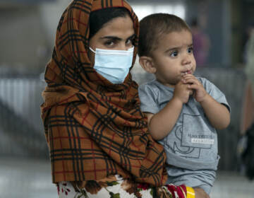 An Afghan woman wearing a face mask holds a child