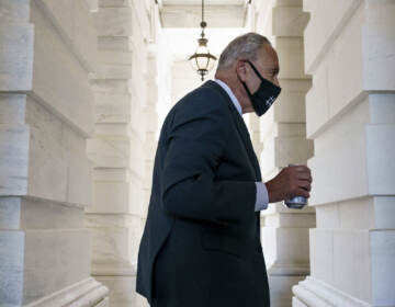 Chuck Schumer walks while carrying a beverage and wearing a mask