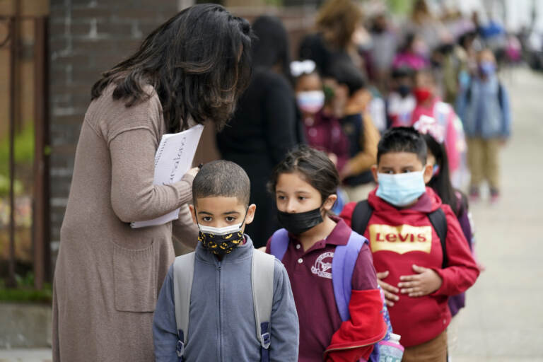 Students wearing face masks line up to enter Christa McAuliffe School
