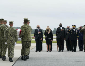 President Joe Biden watches as a Navy carry team moves a transfer case containing the remains of Navy Corpsman Maxton W. Soviak
