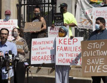 People from a coalition of housing justice groups hold signs protesting evictions during a news conference