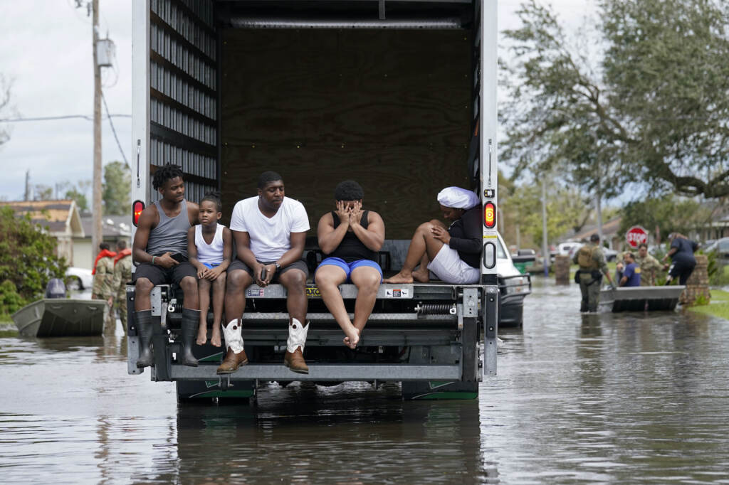A family sits on the back of a truck amid floodwaters