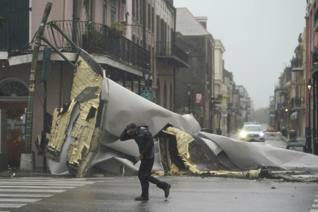 A man passes by a section of roof that was blown off of a building in the French Quarter