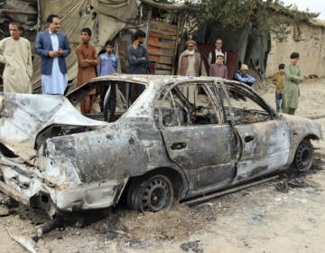 Locals view a vehicle damaged by a rocket attack in Kabul