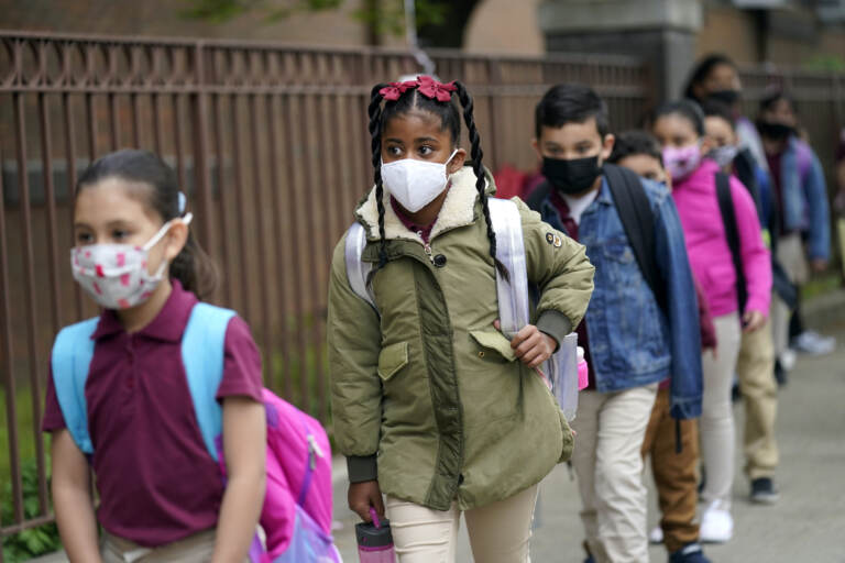 Students line up to enter Christa McAuliffe School while wearing masks