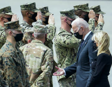 President Joe Biden holds a presidential challenge coin as he is surrounded by Air Force officers