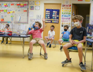 Kindergarteners wear face masks while sitting in a classroom