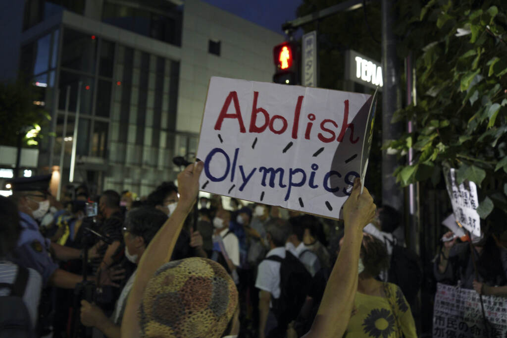 """An anti-Olympic protester holds up a sign that says, """"Abolish Olympics"""""""