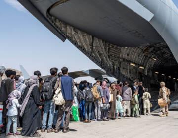 U.S. Airmen and Marines guide Afghan evacuees aboard a U.S. Air Force C-17 Globemaster III at Hamid Karzai International Airport in Kabul