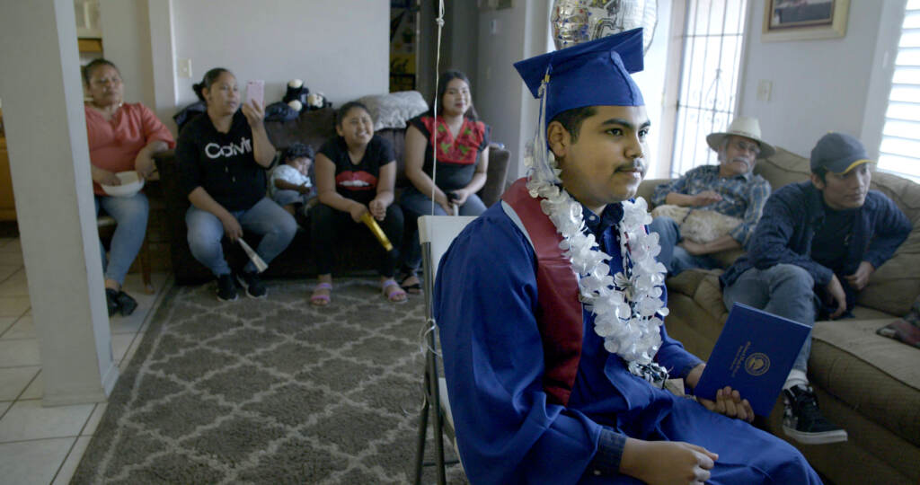 """A still from the documentary """"Homeroom"""" shows a person wearing a graduation gown, with people sitting on a couch behind them"""