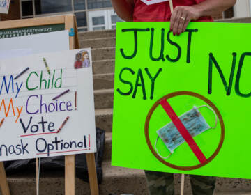 Two parents held signs outside the North Penn school district board meeting against mask mandates in the classrooms
