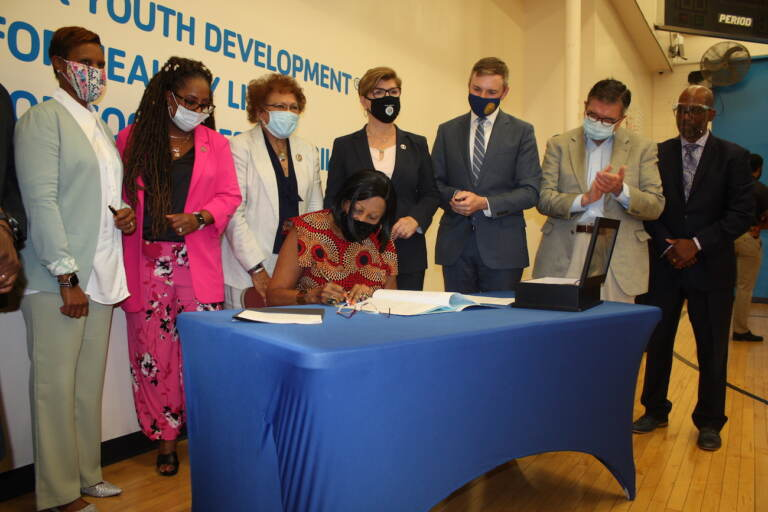 N.J. Lt. Gov. Sheila Oliver - as acting governor - signs into law a bill that sets asides more than $8 million over two years to pilot a program in four cities that will help youth offenders get reintegrated into the community. (P. Kenneth Burns/WHYY)