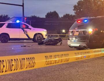 A motorcycle is pictured beside police vehicles and crime scene tape