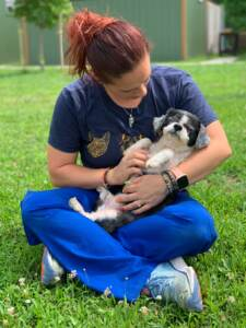 A person holds Gucci the pup in her arms while sitting on the grass outside