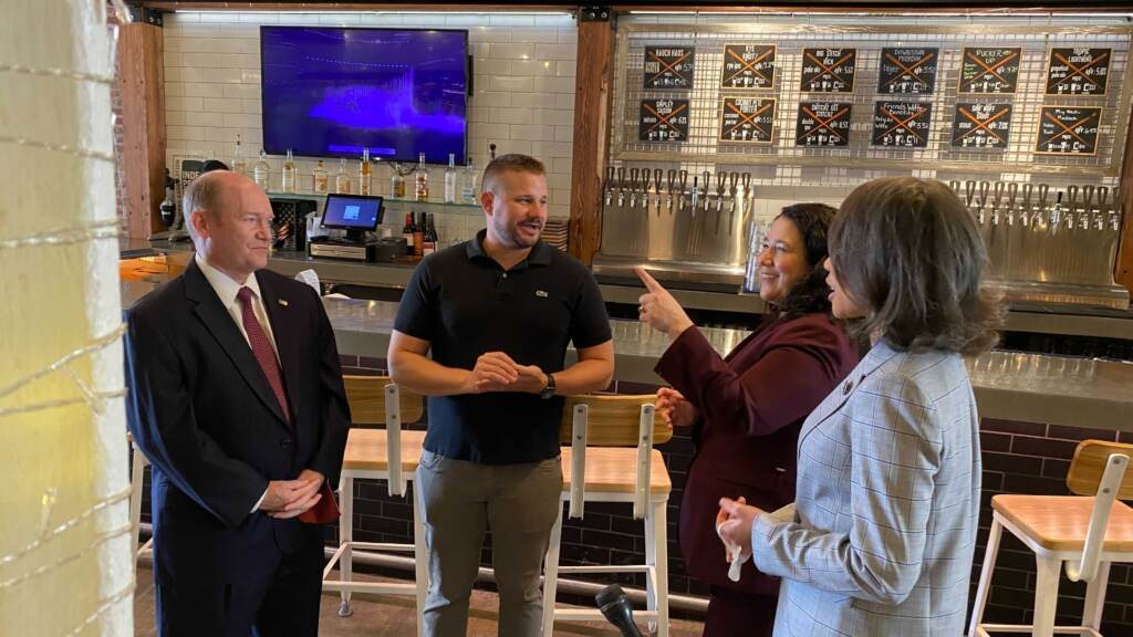 Isabella Casillas Guzman (second from right) talks with Stitch House Brewery co-owner Rob Snowberger during a tour of Wilmington businesses with U.S. Sen. Chris Coons and U.S. Rep. Lisa Blunt Rochester