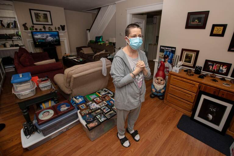 Stacey Horrocks stands inside her home wearing a face mask