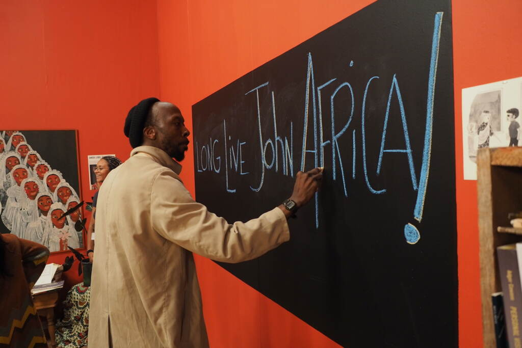"""A still from """"The Inheritance"""" shows a man at a chalkboard, with the words """"Long live John Africa"""" written"""