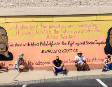 Teenagers sitting in front of a mural with George Floyd and Breanna Taylor in support of Black Lives Matter