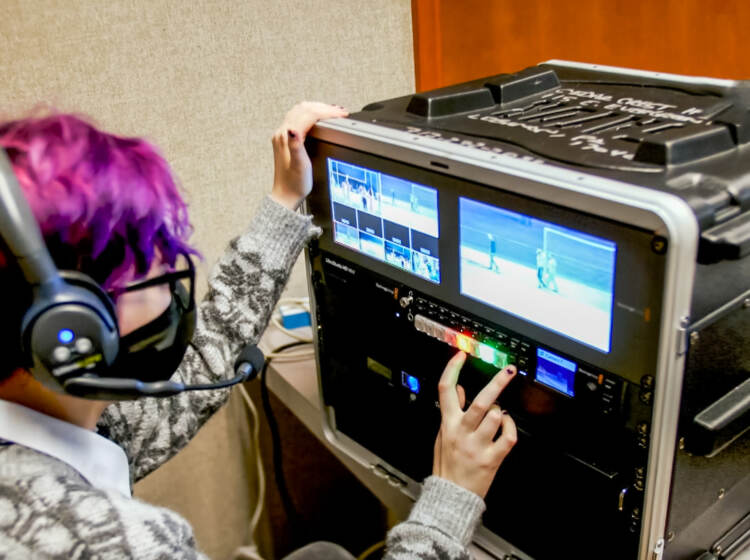 A teenage girl working on a broadcast monitor