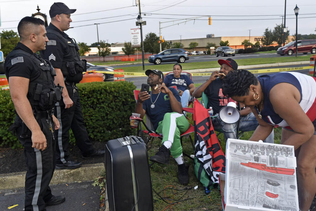 amden activist Gary Frazier (center) and other protesters eat pizza and chat with Deptford police officers