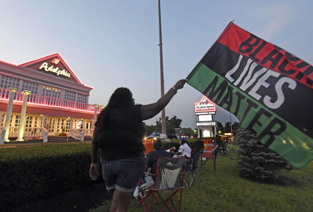 Clarkiya Wilson waves a Black Lives Matter flag outside Adelphia restaurant