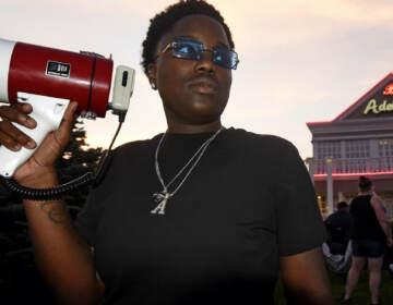 Protester Ajahnae Weal holds a bullhorn outside Adelphia restaruant