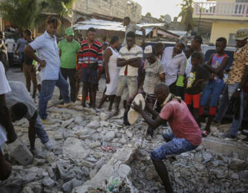 A man digs with a stone through the rubble of a house destroyed by the earthquake in Les Cayes