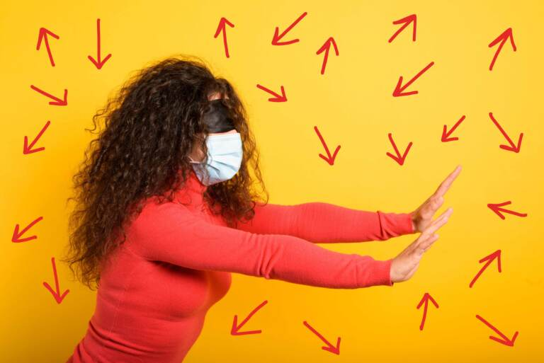Woman with mask and blindfold has her arms out trying to find her way, expressing uncertainty