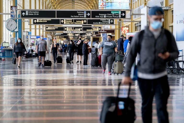 Travelers wearing protective masks walk through Ronald Reagan National Airport in Arlington, Va., in May. (Stefani Reynolds/Bloomberg via Getty Images)