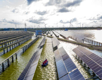 Electrical workers check solar panels at a photovoltaic power station built in a fishpond in Haian in China's eastern Jiangsu province. (STR/AFP via Getty Images)