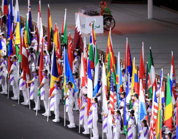 The flags of the participating nations are displayed in the parade of athletes during the opening ceremony of the Tokyo 2020 Paralympic Games