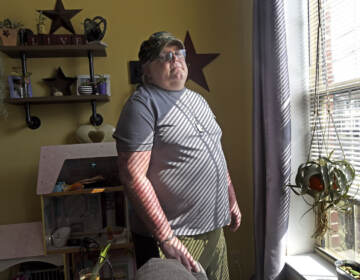 In Camden on August 6, Antioch Manor resident Don Brown stands at the window in his apartment; from it, he watched a murder take place earlier this year. (April Saul for WHYY)