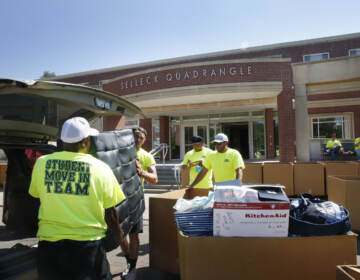 Workers help students move in to Selleck Hall