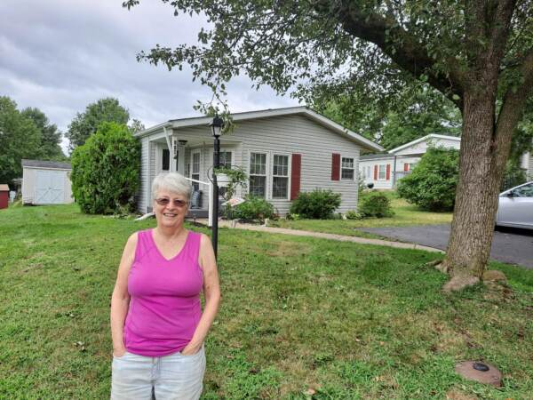 Kathie Sessinger stands in front of her home