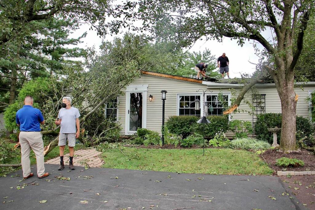 Contractors assess damage to a home in Hidden Springs