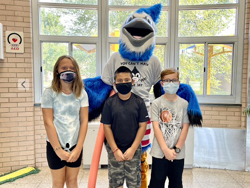Three students wearing masks stand in front of a mascot