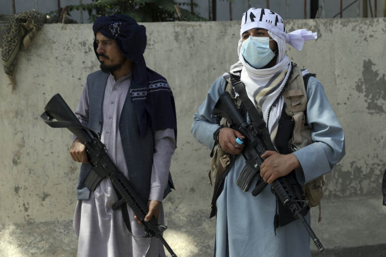 Taliban fighters stand guard in the main gate leading to Afghan presidential palace, in Kabul, Afghanistan, Monday, Aug. 16, 2021. The U.S. military has taken over Afghanistan's airspace as it struggles to manage a chaotic evacuation after the Taliban rolled into the capital. (AP Photo/Rahmat Gul)