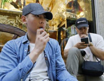 In this Monday, June 17, 2019, file photo, Joshua Ni, 24, and Fritz Ramirez, 23, vape from electronic cigarettes in San Francisco. (AP Photo/Samantha Maldonado, File)