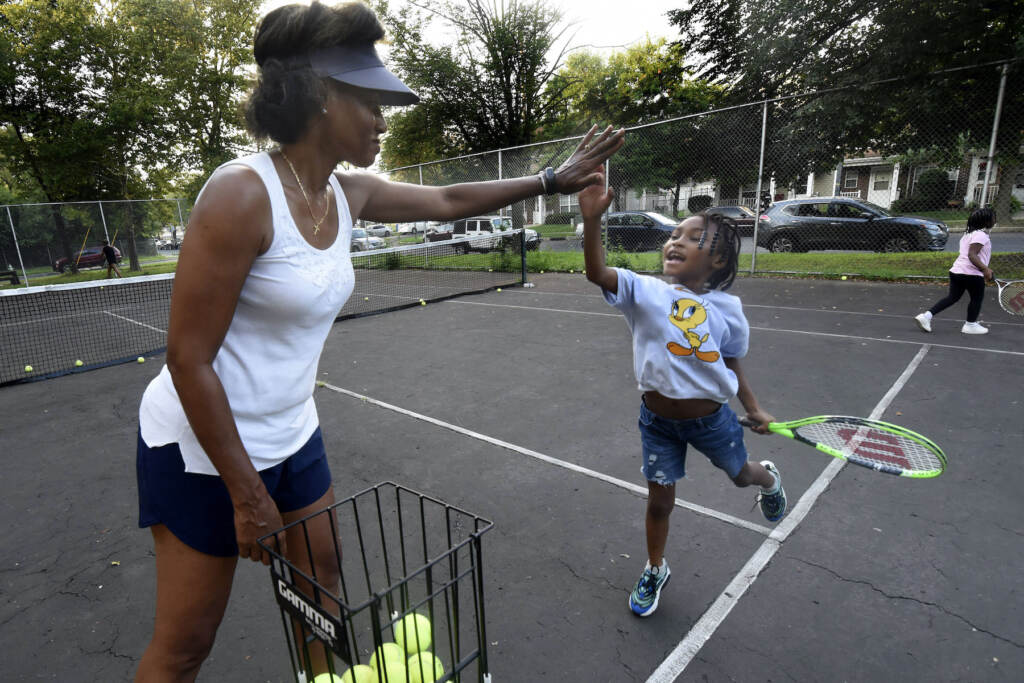 Kelly Cass-White gets a high-five from tennis student Harlem Lewis, 6 on Aug. 26, 2021