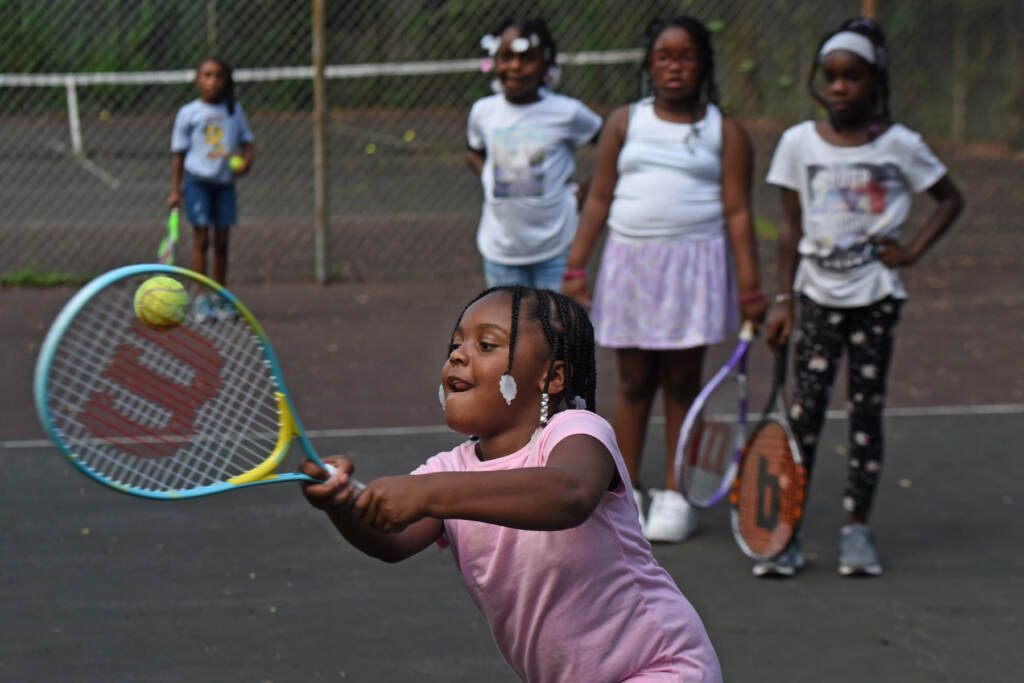 Dennyleona Perry, 5, learns to play tennis in Camden on Aug. 26, 2021
