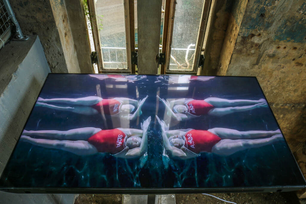 A video screen shows swimmers in the water