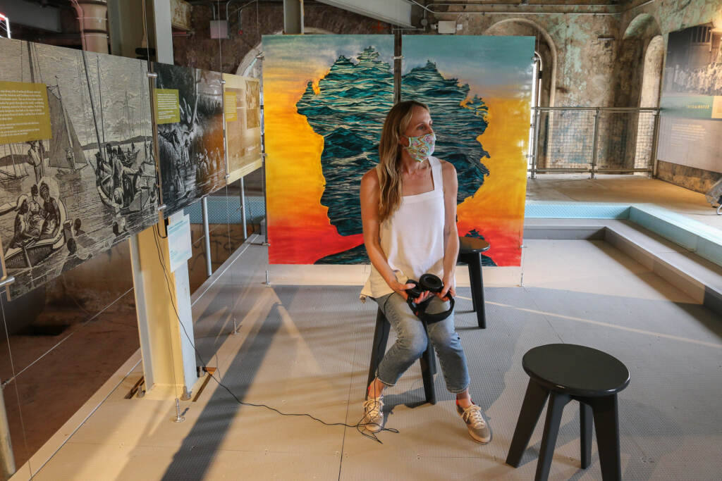 Victoria Prizzia sits with a camera at an art exhibit
