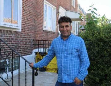 Mohammed Sadeed stands with his hand on a railing outside his home