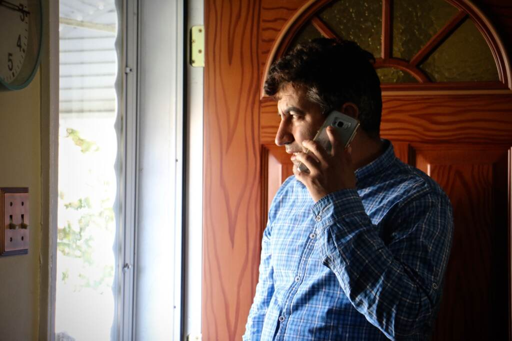 Mohammed Sadeed holds a phone to his ear as he stands by his front door