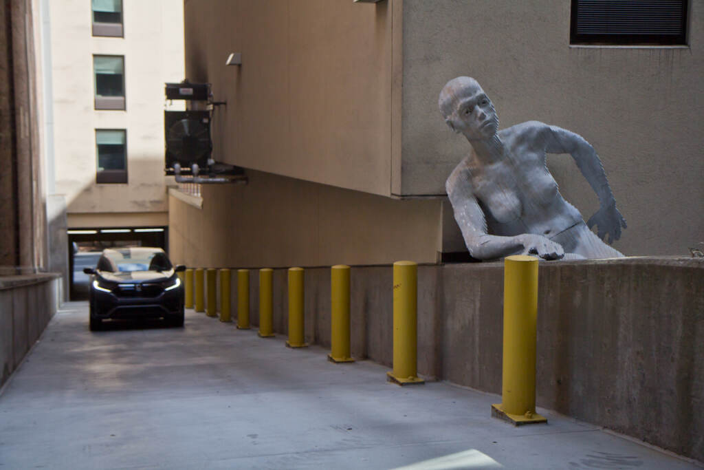 A driver enters the parking garage on 13th and Cuthbert streets, where a statue is pictured